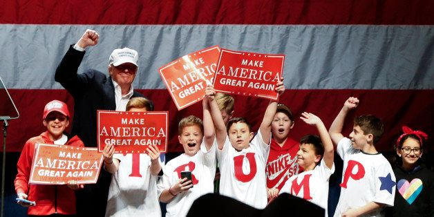 Republican presidential candidate Donald Trump poses with children on stage at a campaign rally in Sterling Heights, Mich., S