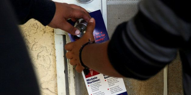 Juan Munoz, 18, and America Najera, 32, of the Democratic Party of Orange County leave a door hanger featuring an image of Do