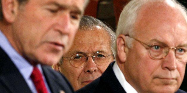 U.S. Secretary of Defense Donald Rumsfeld (C) and Vice President Dick Cheney listen to U.S. President George W. Bush speak be