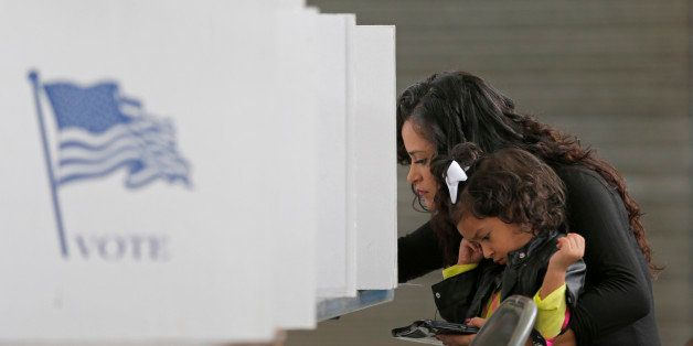 Betsy Argueta holds her daughter Isabella, 2, as she votes in the U.S. presidential election at the National Guard Armory in
