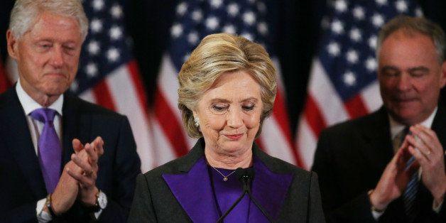 Hillary Clinton, accompanied by her husband former U.S. President Bill Clinton (L) and running mate Senator Tim Kaine, addres