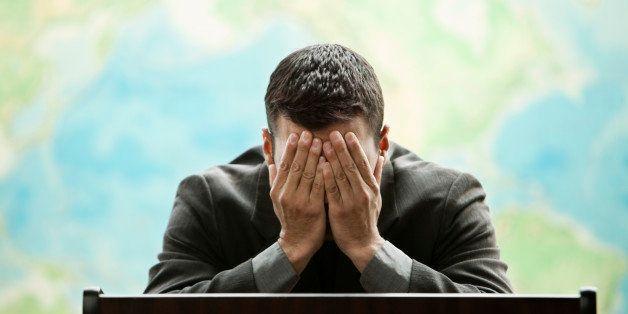Frustrated Hispanic businessman standing at podium