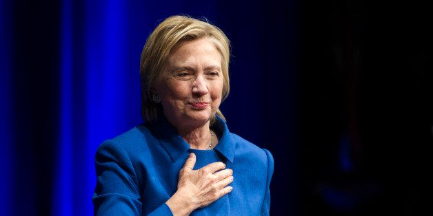 Hillary Clinton places her hand over her hand as she walks to the podium to address the Children's Defense Fund's Beat the Od