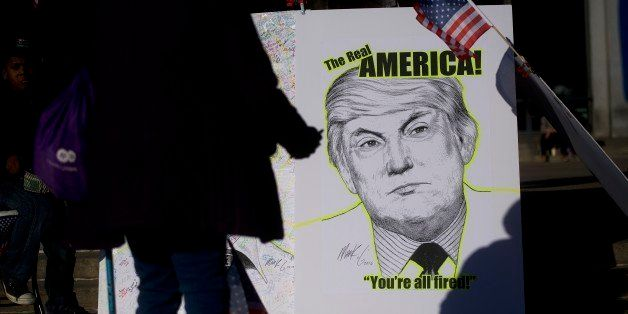 PHILADELPHIA, PA - NOVEMBER 19:  Artist Mark G displays artwork for signatures during a protest against President-elect Donal