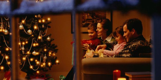 Family opening gifts on Christmas Eve, viewed through window