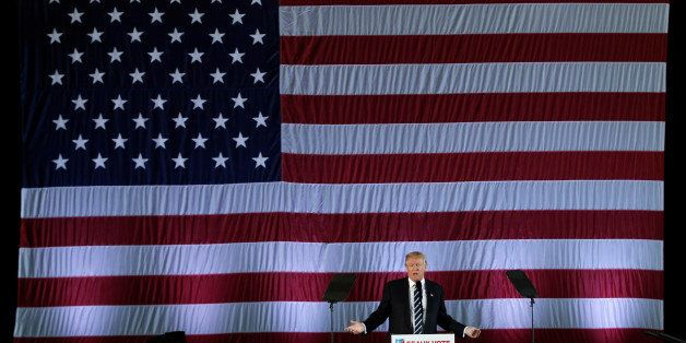"""U.S. President-elect Donald Trump speaks beneath a giant American Flag during a """"Thank You USA"""" tour rally in Baton Rouge, Lo"""