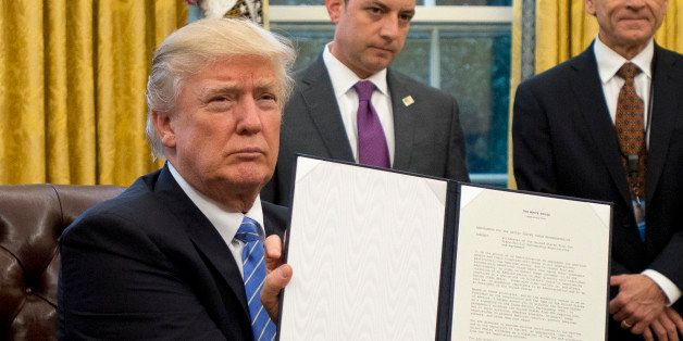 WASHINGTON, DC - JANUARY 23:  (AFP OUT) U.S. President Donald Trump shows the Executive Order withdrawing the US from the Tra
