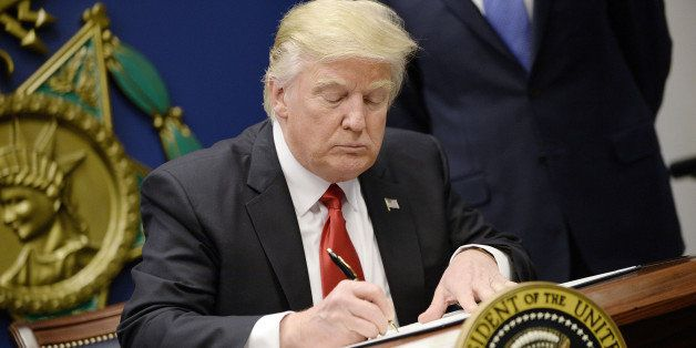 US President Donald Trump signs Executive Orders in the Hall of Heroes at the Department of Defense in Virginia, January 27,