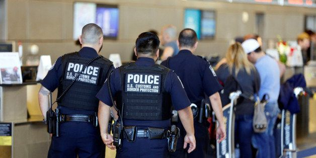 Officers with the U.S. Customs and Border Protection walk past ticket counters during the travel ban at Los Angeles Internati