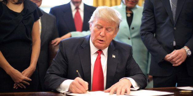 U.S. President Donald Trump signs an executive order cutting regulations, accompanied by small business leaders at the Oval O