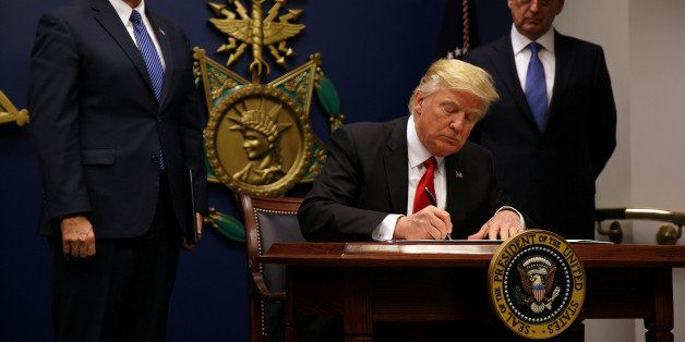 U.S. President Donald Trump signs an executive order he said would impose tighter vetting to prevent foreign terrorists from