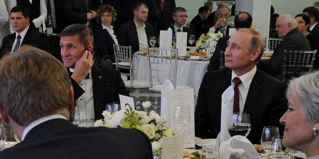 Russian President Vladimir Putin (R) sits next to retired U.S. Army Lieutenant General Michael Flynn (L) as they attend an ex