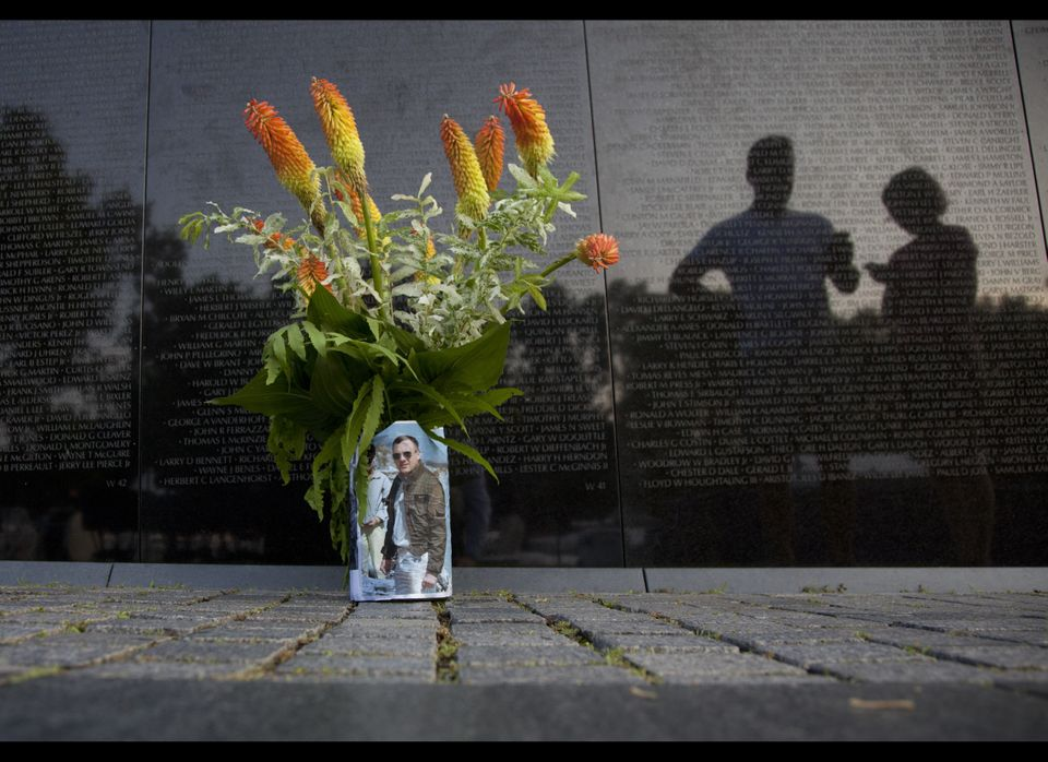 A bouquet of flowers in a can wrapped in a photo is seen as visitors pause along the Vietnam Veterans Memorial Wall on the 50