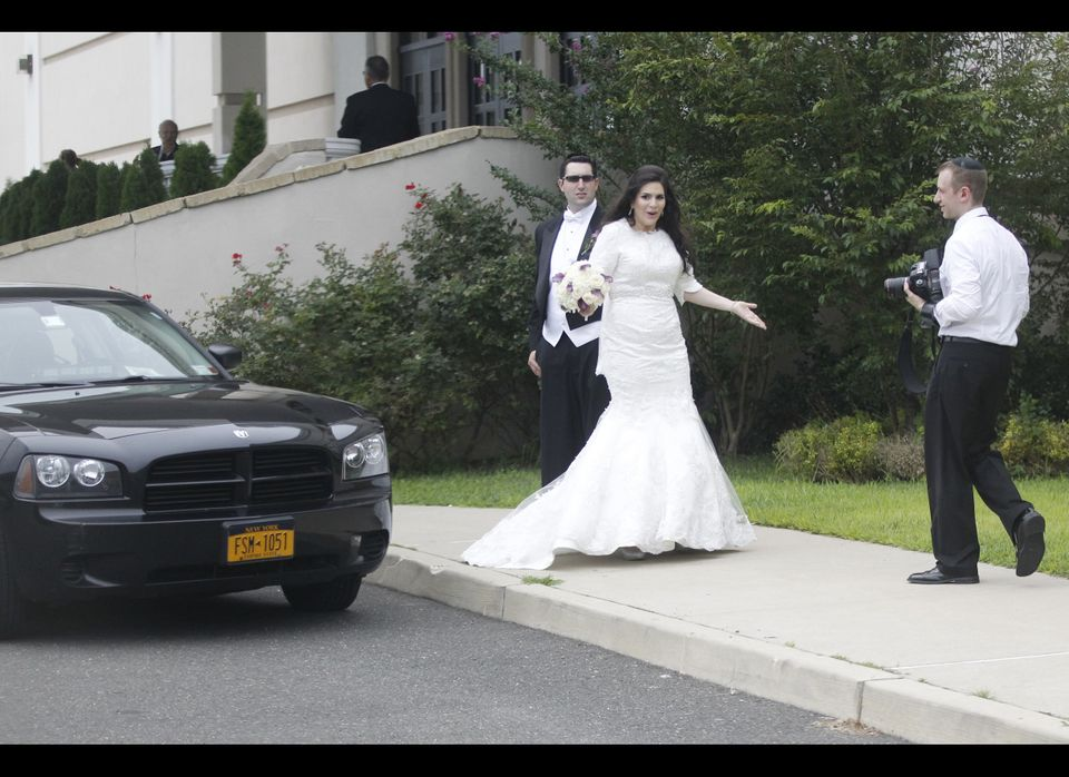 An unidentified bride and groom react at a Jewish wedding as the motorcade of Republican presidential candidate and former Ma