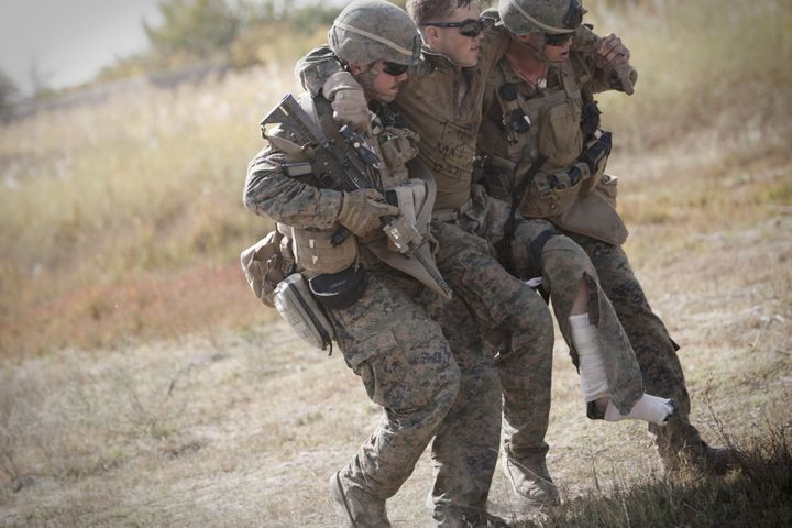 Us Marine lance corporal Zachary Densmor from 3rd Battalion, 7th Marines suffering from fractures in his leg is carried by hi