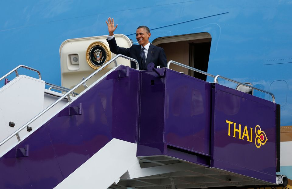 U.S. President Barack Obama waves as he steps off Air Force One at Don Mueang International Airport in Bangkok, Thailand, Sun