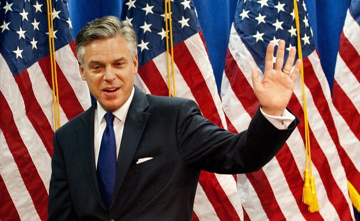 Former Utah Gov. Jon Huntsman waves to a room full of reporters as he leaves after anouncing the suspension of his campaign f