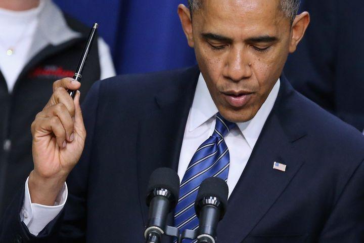 WASHINGTON, DC - NOVEMBER 28:  U.S. President Barack Obama holds a pen while saying he is ready to sign legislation taht woul
