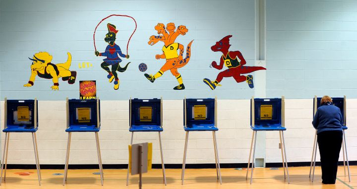 RALEIGH, NC  - NOVEMBER 06:   A voter casts her ballot in the gymnasium of Douglas Elementary School on November 6,  2012 in