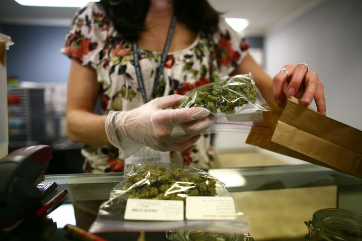 Lakewood, CO - MARCH, 4:  Sales associate, Crystal Guess packages up a patient's cannabis inside a Good Meds medical cannabis