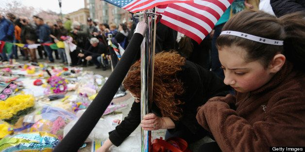 BOSTON, MA - APRIL 20:  People gather at a makeshift memorial for victims near the site of the Boston Marathon bombings a day