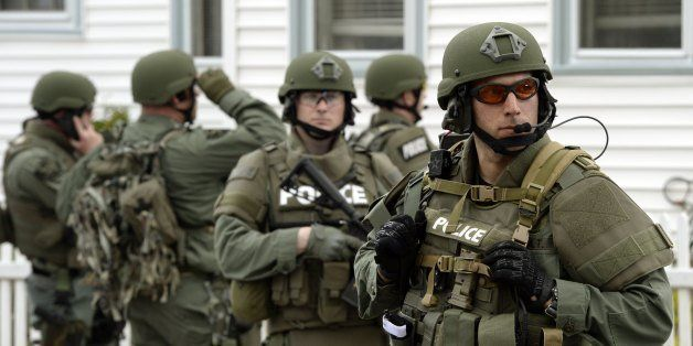 A police SWAT team search houses for the second of two suspects wanted in the Boston Marathon bombings takes place April 19,