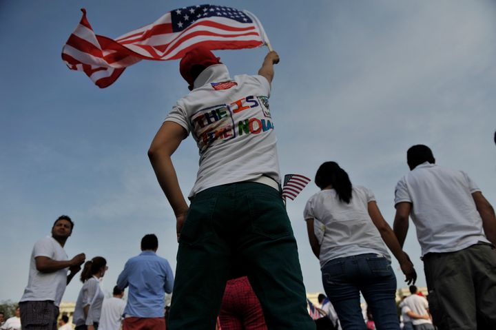 WASHINGTON, DC - APRIL 10: A rally supporter raises an American flag in support of the immigration reform rally on Capitol Hi