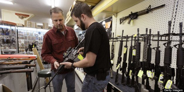 Sales representative Jason Brown, right, shows Steve Levy, of Rolesville, North Carolina, an AR-15 assault rifle manufactured