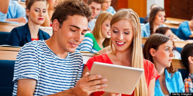 Large group of students sitting in the lecture hall at university. Focus on the young woman and man using a digital tablet to