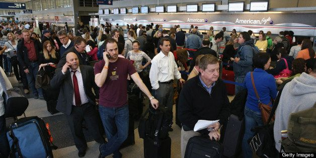 CHICAGO, IL - APRIL 16:  American Airlines passengers wait in line to reschedule flights at O'Hare Airport on April 16, 2013