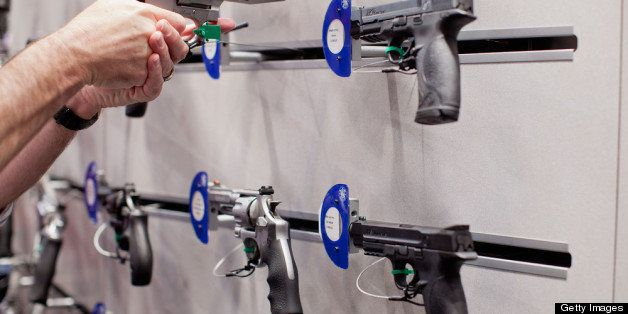 ST. LOUIS, MO - APRIL 14:  A visitor handles a revolver at a Smith & Wesson display during the NRA Annual Meetings and Exhibi