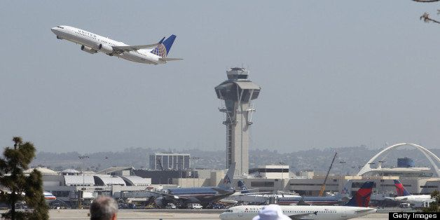 LOS ANGELES, CA - APRIL 22:  People watch as a United Airlines jet passes the air traffic control tower at Los Angles Interna
