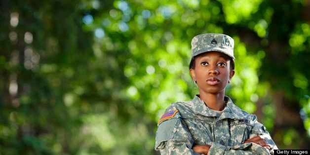 Female African American soldier in army camouflage uniform or ACU and patrol cap.