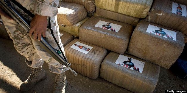 A Mexican soldier stands guard next to packages of marijuana found at a warehouse in Tijuana, Mexico, on Wednesday, Nov. 16,
