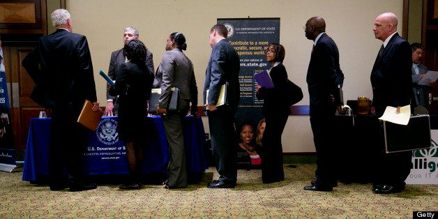 Job seekers wait in line to visit the U.S. Department of State booth at the Choice Career Fairs job fair in Arlington, Virgin