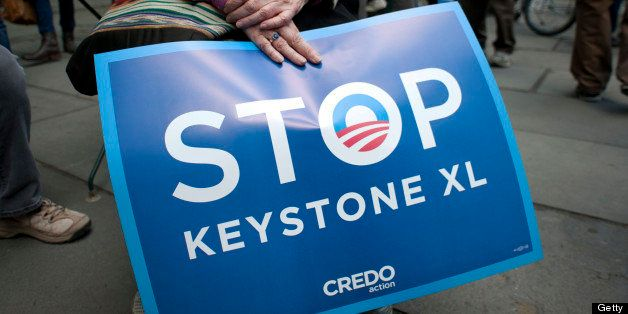 An environmental activist holds a sign in Bryant Park, protesting the proposed Keystone XL pipeline, May 13, 2013 in New York