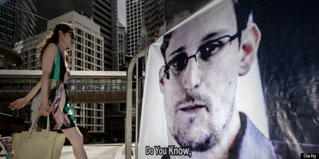 A woman walks past a banner displayed in support of former US spy Edward Snowden in Hong Kong on June 18, 2013.  The 29-year-
