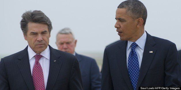 US President Barack Obama speaks with Texas Governor Rick Perry (L) after arriving on Air Force One at Austin-Bergstrom Inter