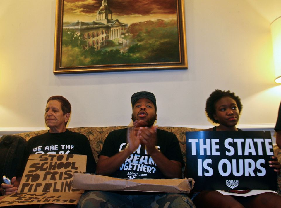 Protestors sit on a couch in Florida Gov. Rick Scott's office Tuesday July 16, 2013 at the Capitol in Tallahassee, Fla. Dream