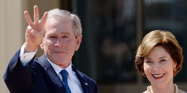 DALLAS, TX - APRIL 25:  Former President George W. Bush shows three fingers for 'W' as his wife and  former first lady Laura