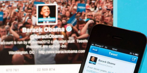 A person poses with a cell phone in front of a computer screen to check Barack Obama's tweet on November 7, 2012 in Paris aft