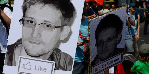 Demonstrators hold placards featuring an image of former US intelligence contractor Edward Snowden as they take part in a pro
