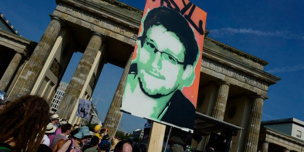 Demonstrators hold up a placard in support of former US agent of the National Security Agency, Edward Snowden in front of Ber