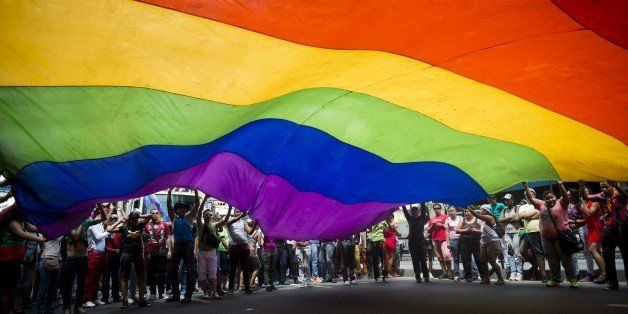 People wave a huge rainbow flag during the 35th Gay Pride Parade in downtown Caracas on June 30, 2013.  AFP PHOTO / Leo RAMIR