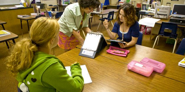 A mentor special education teacher in a Southern California middle school instructs a colleague in administering a psychologi