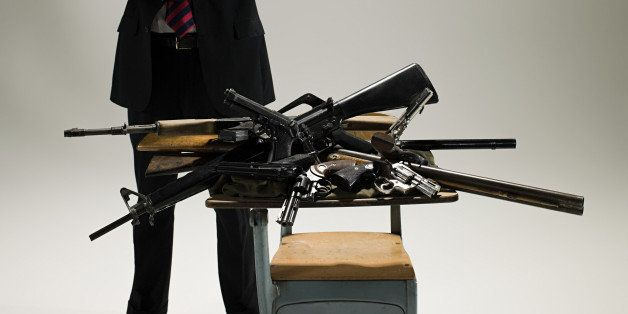 Man with guns on a desk