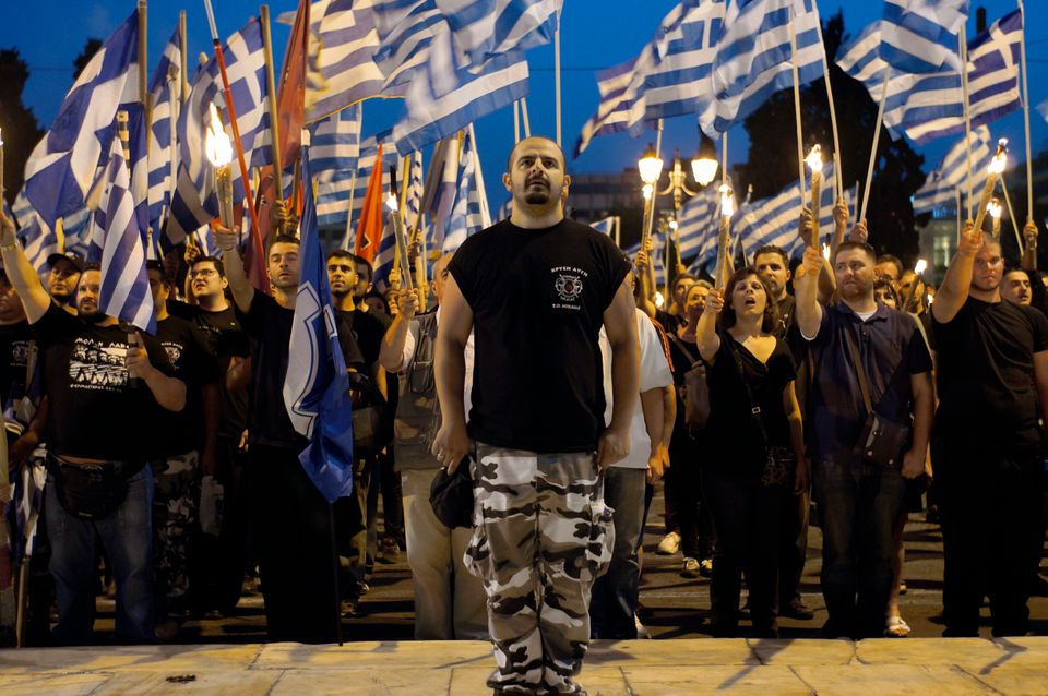 Members and supporters of the ultra-nationalist Golden Dawn party chant the national anthem in front of the Greek parliament