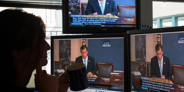 A journalist watches C-SPAN  TV on computer screens showing US Senator Ted Cruz (R-TX) on September 25, 2013 in Washington,DC