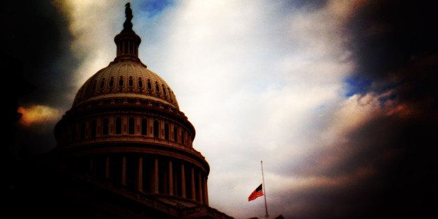 Dramatic post processing of the United States Capitol Building with the United States Flag lowered to half staff.