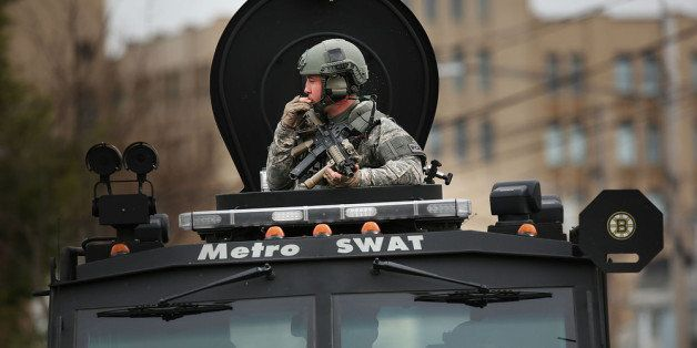 WATERTOWN, MA - APRIL 19:  Members of a police S.W.A.T. team search through a neighborhood in Watertown as they search for 19
